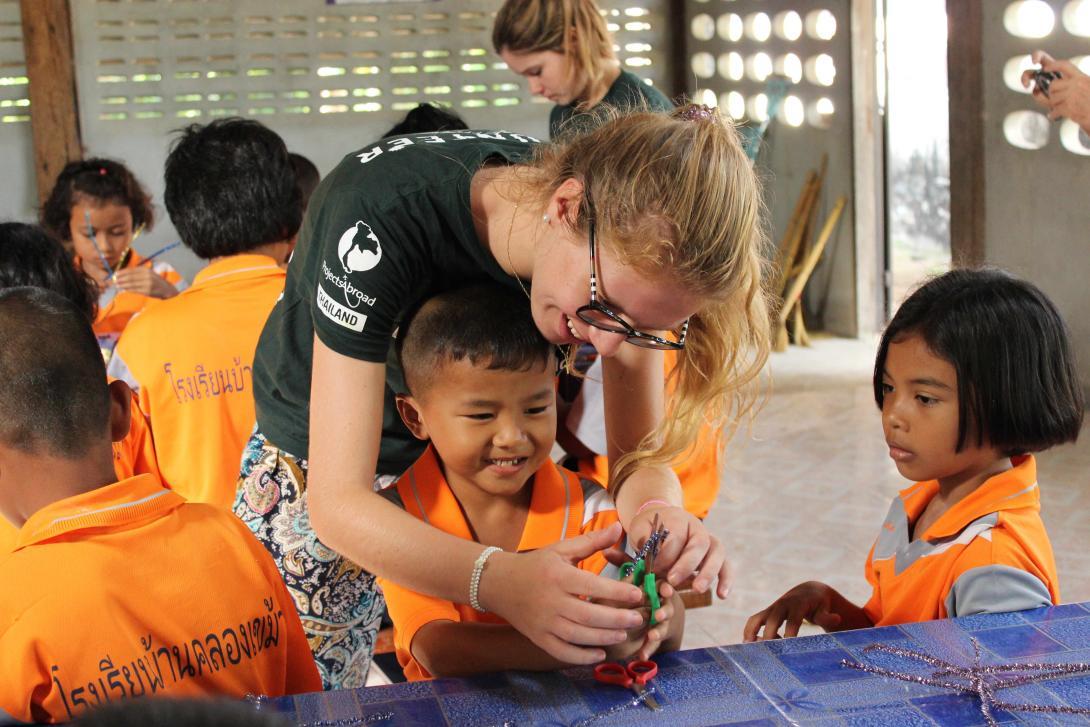 En un voluntariado ético, una voluntaria de Educación en Tailandia ayuda a los niños en una lección de arte.